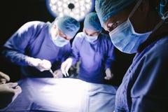 Chirurgen die chirurgie in werkend theater uitvoeren royalty-vrije stock afbeeldingen