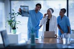Chirurgen die en over röntgenstraal in kliniek bij het ziekenhuis bekijken bespreken stock afbeeldingen