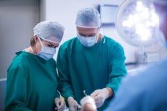 Chirurgen die handeling in verrichtingsruimte uitvoeren royalty-vrije stock afbeelding