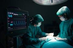 Chirurgenteam die met Toezicht op patiënt in chirurgische werkende ruimte werken royalty-vrije stock afbeelding