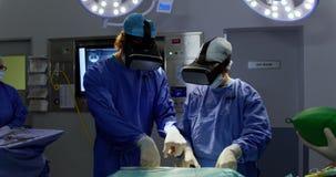 Chirurghi che per mezzo della cuffia avricolare 4k di realtà virtuale video d archivio