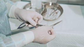 Chirurgicznie stół z bezpłodnymi medycznymi instrumentami Asystent daje chirurgowi skalpela ostrzu Zbliżenie strzelający zbiory wideo