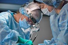 Chirurgie, geneeskunde en mensenconcept - groep chirurgen bij verrichting in werkende ruimte bij het ziekenhuis stock foto