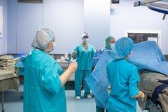 Chirurgie, geneeskunde en mensenconcept - groep chirurgen in werkende ruimte bij ziekenhuis die en spreken het voorbereidingen tr royalty-vrije stock foto