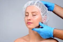 Chirurgie plastique Femme avec des lignes de perforation sur le visage Traitement et lifting anti-vieillissement photographie stock libre de droits