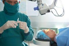 Chirurgien avec la seringue et le patient sur la table photographie stock libre de droits