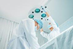 Chirurgien et assistant féminin travaillant dans la salle d'opération Image stock