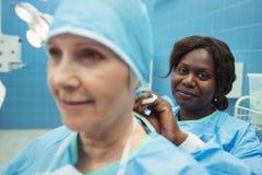 Chirurgien féminin aidant son collègue en utilisant le chapeau chirurgical image libre de droits