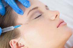 Chirurgien faisant l'injection sur des pieds de corneilles sur le mensonge calme de femme Photo stock