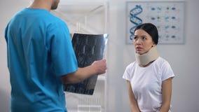 Chirurgien masculin informant le patient féminin dans résultat de rayon X de collier cervical de mousse le mauvais banque de vidéos