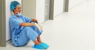 Chirurgien triste s'asseyant sur le plancher dans le couloir banque de vidéos
