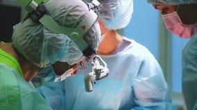 Chirurgiens portant les vêtements de protection exécutant la chirurgie utilisant l'équipement stérilisé Team Performing Surgical  clips vidéos