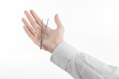 Chirurgisch en Medisch thema: het pincet van de de handholding van een arts op witte achtergrond wordt geïsoleerd die Stock Foto