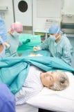 Chirurgisch team dat handeling uitvoert stock afbeelding