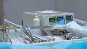 Chirurgische Instrumente und Werkzeuge einschließlich Skalpelle, Zangen und Pinzette vereinbarten auf einer Tabelle für eine Chir stock footage