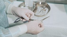 Chirurgische lijst met steriele medische instrumenten De medewerker geeft de chirurg het scalpelblad Close-up wordt geschoten die stock video