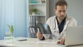 Chirurgo attento che esamina i raggi x dell'osso e che invia email al paziente sul computer portatile video d archivio