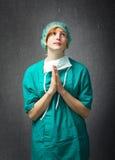 Chirurgo che prega per il perdono immagine stock