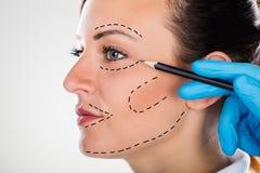 Chirurgo Drawing Correction Lines sul fronte della giovane donna immagini stock libere da diritti