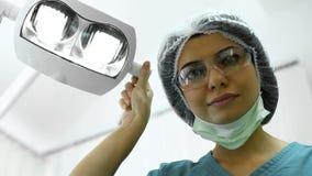 Chirurgo plastico femminile che regola le luci prima della resezione della talpa, chirurgia plastica immagini stock
