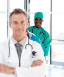 Chirurgo sorridente con le braccia piegate in una riga Fotografia Stock