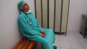 Chirurgo stanco che si siede su un banco video d archivio