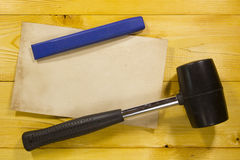 Chisel and black rubber hammer. On a brown wooden background stock image