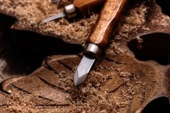 Chisel on a block of carved wood with shavings. And sawdust royalty free stock photo