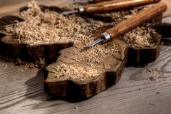 Chisel on a block of carved wood with shavings. And sawdust stock image