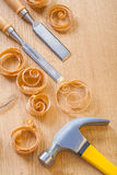 Chisel and claw hammer with wooden shavings on board Stock Photography