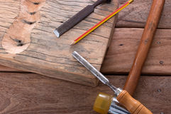 The chisel hammering on wood. The chisel hammering and pencil on wooden working stock image