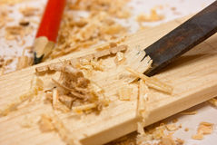 Chisel, sawdust and wood plaque. Chisel, sawdust, red pencil and wood plaque stock photography