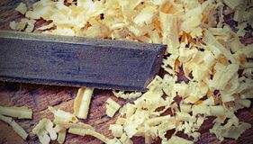 Chisel and shavings on the workbench of  carpenter. With old toned effect stock image