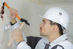 Chisel worker in breaking plaster. Chisel worker in breaking the plaster stock images