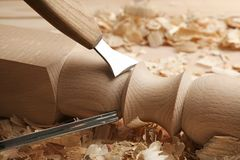 Chiseling wooden part in carpenter`s workshop. Closeup royalty free stock photo
