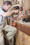 Chiseling on workbench. Older man using chisel on workbench Royalty Free Stock Photos