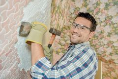 Chiselling old motif off wall. Chiselling old motif off a wall Stock Photos