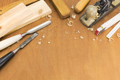 Chisels and plane with shavings on wooden background Royalty Free Stock Photography