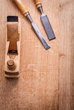 Chisels and woodworkers plane on wooden board Stock Photos