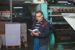 CHISINAU, МОЛДАВИЯ - 26-ОЕ АПРЕЛЯ 2016: Работники в доме печатания Люди работая на печатной машине в фабрике печати Промышленное  Стоковая Фотография