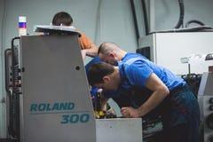 CHISINAU, МОЛДАВИЯ - 26-ОЕ АПРЕЛЯ 2016: Работники в доме печатания Люди работая на печатной машине в фабрике печати Промышленное  Стоковые Фотографии RF