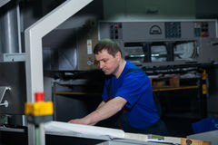 CHISINAU, МОЛДАВИЯ - 26-ОЕ АПРЕЛЯ 2016: Работники в доме печатания Люди работая на печатной машине в фабрике печати Промышленное  Стоковые Изображения RF