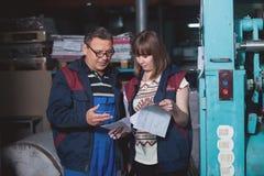 CHISINAU, МОЛДАВИЯ - 26-ОЕ АПРЕЛЯ 2016: Работники в доме печатания Люди работая на печатной машине в фабрике печати Промышленное  Стоковые Фото