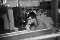 CHISINAU, MOLDAU - 26. APRIL 2016: Arbeitskräfte im Druckhaus Leute, die an Druckmaschine in der Druckfabrik arbeiten Industriell Lizenzfreie Stockfotografie