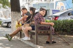 CHISINAU, MOLDAVIA - 11 AGOSTO 2015: Donna anziana che si siede su un banco accanto ad una giovane coppia, la donna che è incinta Fotografia Stock
