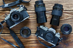 Chisinau Moldavien - Jule 06, 2017: Två tappningfilmkameror Minolta XD 7 och Minolta X-300 och linser på träbackgr Royaltyfri Foto