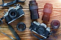 Chisinau Moldavien - Jule 06, 2017: Två tappningfilmkameror Minolta XD 7 och Minolta X-300 och linser på träbackgr Arkivbilder