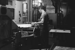 CHISINAU, MOLDOVA - APRIL 26, 2016: Workers in printing house. People working on printing machine in print factory. Industrial wor