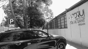 Porsche SUV parked in front of Codru Restaurant in Chisinau city center. CHISINAU, MOLDOVA - CIRCA 2018: Soviet Codru Restaurant facade in Chisinau city center stock video