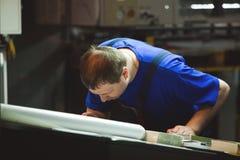 CHISINAU, MOLDOVA - 26 DE ABRIL DE 2016: Trabalhadores na casa de impressão Povos que trabalham na máquina de impressão na fábric Imagens de Stock